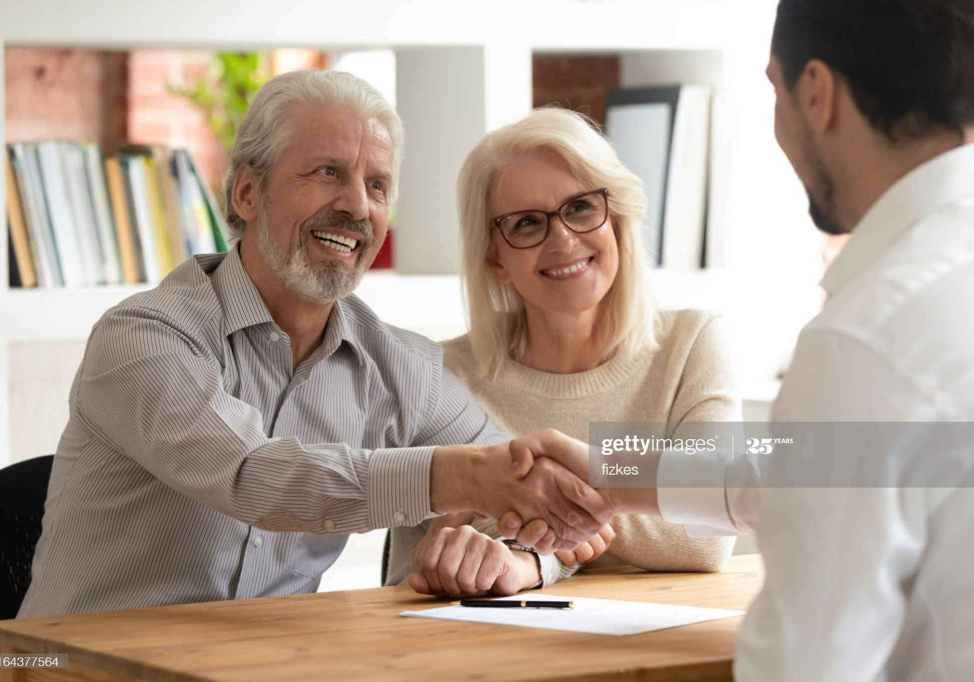 Happy senior old family couple clients make financial insurance estate business deal handshake agent lawyer, satisfied mature customers shake hand meeting bank manager agree on investment contract