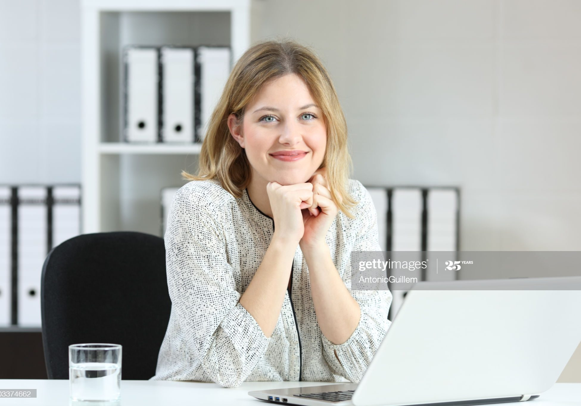 Front view portrait of a businesswoman posing looking at you on a desk at office
